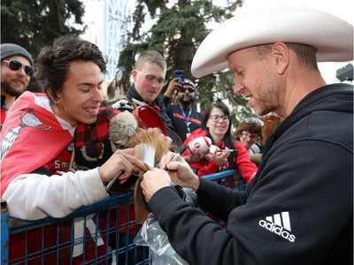 The Calgary Stampeders Head Coach Dave Dickenson signs autographs as thousands of fans turned out for a rally celebrating the Calgary Stampeders victory in the 106th Grey Cup outside city hall in Calgary on Tuesday, Nov. 27, 2018.