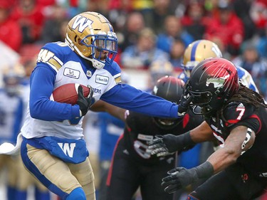 Winnipeg Blue Bombers RB Nic Demski (L) runs the ball and is defended by Stamps Junior Turner (7) during the CFL Western Final in Calgary at McMahon Stadium on Sunday, November 18, 2018. Jim Wells/Postmedia