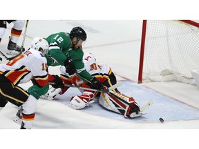 Dallas Stars center Radek Faksa (12) gets the puck past Calgary Flames goaltender David Rittich (33) and Matthew Tkachuk (19) scoring a goal during the second period of an NHL hockey game in Dallas, Tuesday.