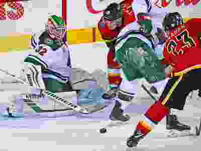 The Calgary Flames' Sean Monahan and Matthew Tkachuk look to grab a loose puck in front of goaltender Alex Stalock NHL action at the Scotiabank Saddledome in Calgary on Thursday December 6, 2018.