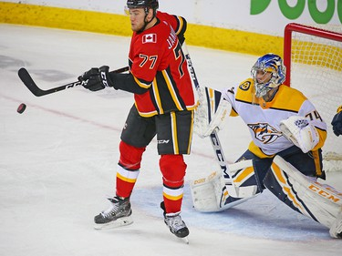 The Calgary Flames' Mark Jankowski swings for a flying puck in front of Nashville Predators goaltender Juuse Saros during NHL action at the Scotiabank Saddledome in Calgary on Saturday December 8, 2018.