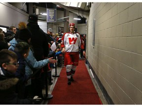 Calgary Hitmen players walk to the team dressing room at the Corral before they play the Prince Albert Raiders on Friday at the Corral. Photo by Leah Hennel/Postmedia.