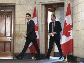 Prime Minister Justin Trudeau leaves his office with his principal secretary Gerald Butts to attend an emergency cabinet meeting on Parliament Hill in Ottawa on Tuesday, April 10, 2018. Butts has resigned amid allegations that the Prime Minister's Office interfered to prevent criminal prosecution of SNC-Lavalin.
