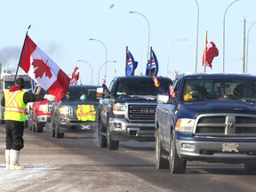 Martin Zobrist greets truckers and supporters as he stands on Highway 1 in Strathmore, AB, 45 km east of Calgary on Thursday, February 14, 2019 as the United We Roll convoy for Canada is eastbound to Ottawa. Zobrist said he left work in Calgary for the day. Jim Wells/Postmedia