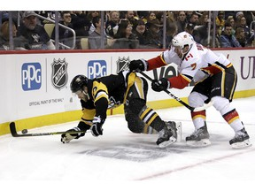 Calgary Flames blueliner TJ Brodie (7) checks Pittsburgh Penguins' Bryan Rust (17) off the puck during the second period of an NHL hockey game in Pittsburgh, Saturday, Feb. 16, 2019.