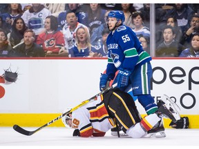 Calgary Flames' James Neal, bottom, holds his mouth after taking a high stick to the face from Vancouver Canucks' Alex Biega (55) and losing teeth during third period NHL hockey action in Vancouver on Saturday, Feb. 9, 2019.