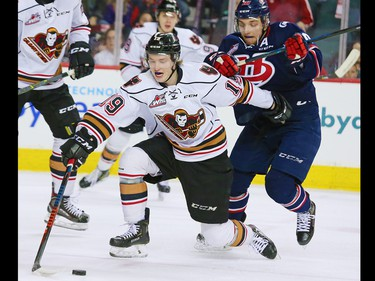 Calgary Hitmen Carson Focht and the Lethbridge Hurricanes' Jake Leschyshyn race for the puck during their play-off game in Calgary on Sunday, March 31, 2019. The Hurricanes won the game 7-6 in overtime forcing a seventh game back in Lethbridge.