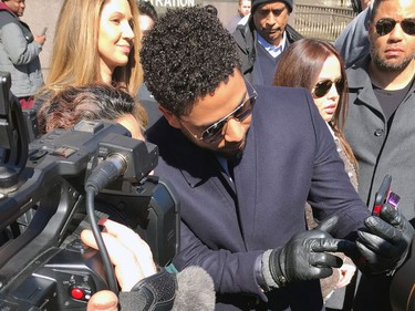 "Empire actor Jussie Smollett appears with a fan as he walks out of the Leighton Criminal Court Building after a hearing Tuesday, March 26, 2019, in Chicago. Smollett attorneys Tina Glandian and Patricia Brown Holmes said in a statement Tuesday that Smollett's record ""has been wiped clean."" Smollett was indicted on 16 felony counts related to making a false report that he was attacked by two men who shouted racial and homophobic slurs."
