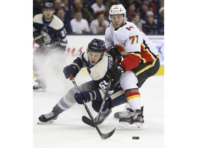 Calgary Flames' Mark Jankowski, right, and Columbus Blue Jackets' Markus Nutivaara, of Finland, chase a loose puck during the first period of an NHL hockey game Tuesday, Dec. 4, 2018, in Columbus, Ohio.