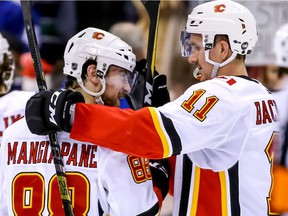 Calgary Flames' Andrew Mangiapane (88) and teammate Mikael Backlund (11) celebrate their teams win after NHL hockey action against the Vancouver Canucks, in Vancouver on Saturday, March 23, 2019.