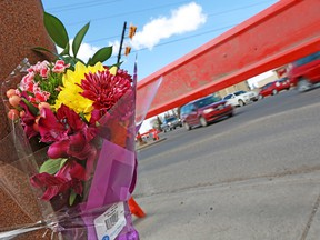 A bouquet of flowers is taped to a light post at 32nd Avenue and 26th Street N.E. where a pedestrian was killed on Monday, April 22, 2018.