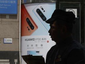 In this photo taken Thursday, May 16, 2019, a man handing out pamphlets is silhouetted against a advertisement for the latest smartphones from Huawei in Beijing.