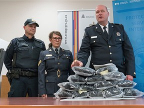 Border Services officer Cody Uytterhagen, left, RCMP Cpl. and Sharon Franks listen to CBSA Superintendent Darryl Anderson as he makes a statement regarding the seizure of 14.5kg of suspected methamphetamine in Southern, Alberta.   At the news conference in Raymond, Alberta, Friday, February 5, 2016, RCMP said they have charged Season, Truax, of Calgary with three counts under the Customs Act.