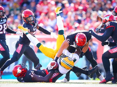 Edmonton Eskimos Natey Adjei is tackled by Cordarro Law and Cory Greenwood Calgary Stampeders during CFL football in Calgary on Monday, September 2, 2019. Al Charest/Postmedia