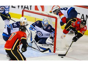 Calgary Flames Andrew Mangiapane attempts the wrap - around on goalie Eric Comrie of the Winnipeg Jets during pre-season NHL hockey in Calgary on Tuesday September 24, 2019. Al Charest / Postmedia