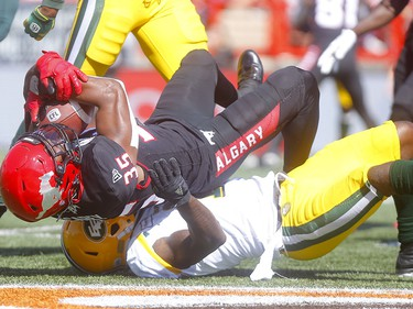 Calgary Stampeders, Ka'Deem Carey is tackled by Edminton Eskimos, Larry Dean in first half action in the Labour Day classic at McMahon stadium in Calgary on Monday, September 2, 2019. Darren Makowichuk/Postmedia