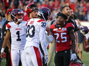 The Calgary Stampeders' Don Jackson talks with the Montreal Alouettes Jarnor Jones as they await a review after Eric Rogers' touchdown pass. The pass was eventually ruled caught out of bounds ending the Stampeders chance in overtime against the Montreal Alouettes during CFL action in Calgary on Saturday August 17, 2019. The Alouettes won 40-34. Gavin Young/Postmedia
