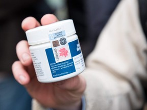 A customer shows a marijuana product that he bought after entering a cannabis store on October 17, 2018 in Montreal, Quebec.