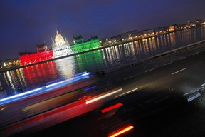 The building of the Hungarian Parliament is lighted by national tricolor lights to commemorate the 1956 uprising against Soviet occupation during the national day on the bank of the river Danube in downtown Budapest, on October 23, 2009. Hungary's uprising which erupted on October 23, 1956 and was crushed by Soviet tanks on November 4, sealing the country's fate as a satellite state of Moscow until the fall of the Iron Curtain in 1989. AFP PHOTO / FERENC ISZA (Photo credit should read FERENC ISZA/AFP/Getty Images)