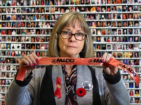 Denise Dubyk with MADD Calgary stands in front of a memorial wall to Canadian victims of impaired drivers at the launch of the annual Project Red Ribbon campaign to prevent impaired driving over the holiday season.
