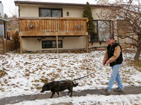 Chris Wentworth walks his dog Lucy past a house at 1040 Ranchlands Blvd. N.W. the morning after 7 dogs died in a smoky fire in the home Monday night, November 11, 2019. Wentworth who lives nearby was saddened to hear so many dogs had died. Gavin Young/Postmedia
