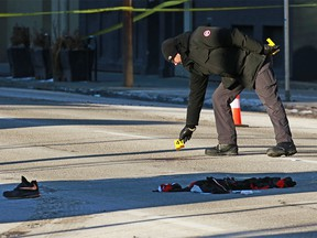 Crime scene investigators place evidence markers at the scene of an early morning suspicious death along 11th Avenue near 1st Street S.W. in Calgary on Sunday, January 5, 2020.