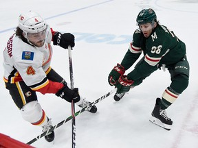 ST PAUL, MINNESOTA - JANUARY 05: Rasmus Andersson #4 of the Calgary Flames and Ryan Hartman #38 of the Minnesota Wild go after the puck during the second period during the game at Xcel Energy Center on January 5, 2020 in St Paul, Minnesota. (Photo by Hannah Foslien/Getty Images)