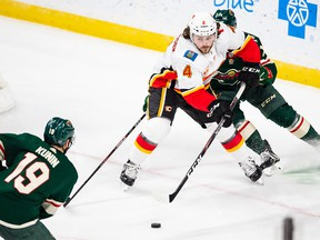 Flames defenceman Rasmus Andersson protects the puck against the Minnesota Wild.