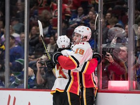 CP-Web.  Calgary Flames' Matthew Tkachuk (19) and Johnny Gaudreau (13) celebrate Tkachuk's goal against the Vancouver Canucks during the first period of an NHL hockey game in Vancouver, on Saturday February 8, 2020. THE CANADIAN PRESS/Darryl Dyck ORG XMIT: VCRD104
