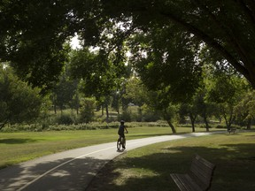 A cyclist rides along a path in Confederation Park during the balmy 21 C temperatures and mostly sunny skies on Friday, August 25, 2017 in Calgary, Alta.