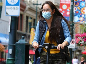 An e-scooter rider wears a mask as she cruises along Stephen Avenue in Calgary on Wednesday, July 15, 2020.