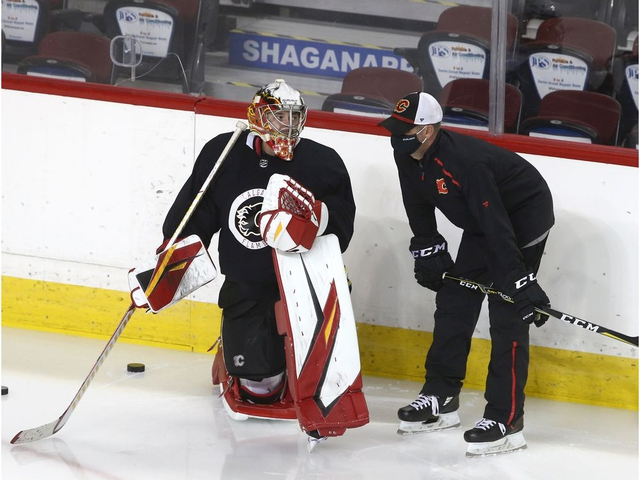 Flames goaltending coach Jordan Sigalet (R) speaks to David Rittich during Calgary Flames training camp a the Saddledome in Calgary on Tuesday, July 14, 2020. Jim Wells/Postmedia