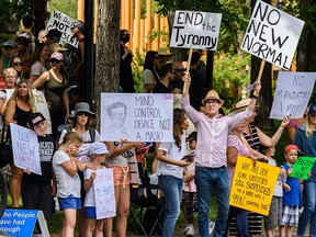 About 150 people gather in Olympic Plaza near city hall in downtown Calgary to protest against potential mandatory masks on Sunday, July 19, 2020.