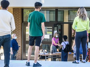 Students wait in line outside St. Francis High School for their diploma exam on Tuesday, August 4, 2020.