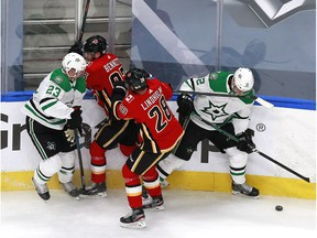 Radek Faksa #12 and Esa Lindell #23 of the Dallas Stars battle for the puck with Elias Lindholm #28 and Sam Bennett #93 of the Calgary Flames during the first period in Game Two of the Western Conference First Round during the 2020 NHL Stanley Cup Playoffs at Rogers Place on August 14, 2020 in Edmonton, Alberta, Canada. (Photo by Jeff Vinnick/Getty Images)