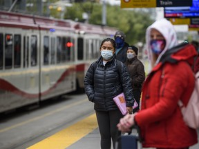 Passengers wait for the train wearing face masks at City Hall station on Tuesday, Sept. 15, 2020.