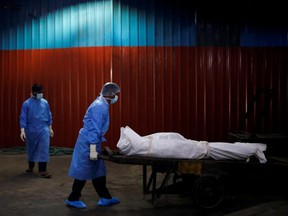 A health worker wearing personal protective equipment carries the body of a man, who died due to COVID-19, at a crematorium in New Delhi, India, Monday, Sept. 7, 2020.