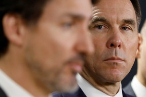 Canada's former minister of finance Bill Morneau is seen here with Prime Minister Justin Trudeau during a press conference in Ottawa on March 11, 2020.