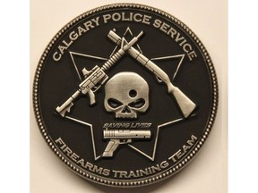 """A Calgary Police Service firearms training team challenge coin depicts a bullet hole through a skull, surrounded by three guns and the phrase """"saving lives."""" Calgary police have prohibited further distribution of the coin, calling the design """"obviously offensive."""""""