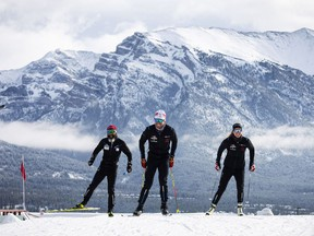 Olympians Dahria Beatty (R), Russell Kennedy (C) and legendary Paralympian, Brian McKeever, get back on snow for the first time in seven months thanks to the world-unique Frozen Thunder snow preservation project at the Canmore Nordic Centre, Monday, October 19, 2020. Photograph by Todd Korol