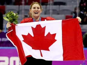 Hayley Wickenheiser celebrates with a flag after Team Canada defeated Team USA 3-2 in overtime to win the women's hockey gold medal at the 2014 Winter Olympics in Sochi, Russia.