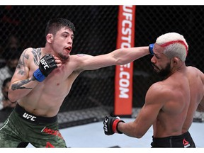 LAS VEGAS, NEVADA - DECEMBER 12:  In this handout image provided by UFC,  (L-R) Brandon Moreno of Mexico punches Deiveson Figueiredo of Brazil in their flyweight championship bout during the UFC 256 event at UFC APEX on December 12, 2020 in Las Vegas, Nevada.