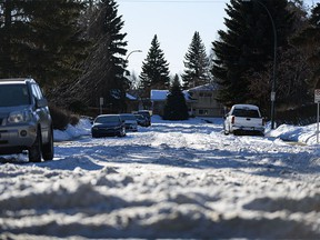 Weeks after the last heavy snowfall, piles of snow in some Calgary streets makes it difficult for drivers to reach the main streets on Thursday, Jan. 7, 2021. Pictured is a street in the northwest community of Varsity.