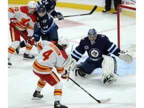 Rasmus Andersson drives the net against Jets goalie Connor Hellebuyck during a recent game.