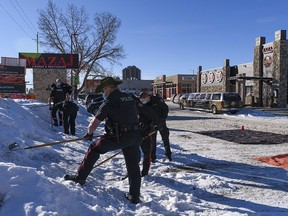 Members of Calgary Police Services rake the snow for evidence at the scene of a suspicious death at the parking lot of Mazaj Lounge and Restaurant on Macleod Trail on Saturday, February 20, 2021.