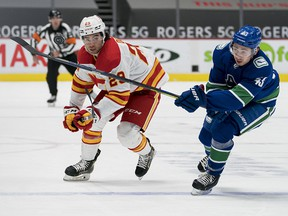 Feb 15, 2021; Vancouver, British Columbia, CAN; Vancouver Canucks defenseman Quinn Hughes (43) checks Calgary Flames forward Dillon Dube (29) in the first period at Rogers Arena.