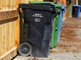 A black cart is shown with compost and recycle bins in an alley in the Elboya community in southwest Calgary Wednesday, April 18, 2018.