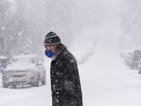 FILE - A masked pedestrian crosses a street in the Beltline as heavy snow sweeps through Calgary on Friday, Feb. 5, 2021.