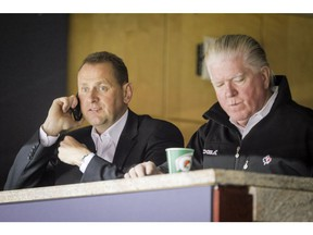 Calgary Flames GM Brad Treliving watches a Flames practice next to Brian Burke, who was the team's president of hockey operations in this photo from October 2014.