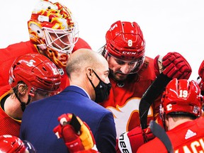 CALGARY, AB - FEBRUARY 9: Assistant coach Ryan Huska of the Calgary Flames talks with Joakim Nordstrom #20, Jacob Markstrom #25, Christopher Tanev #8, Mikael Backlund #11 and Matthew Tkachuk #19 during a time-out in an NHL game against the Winnipeg Jets at Scotiabank Saddledome on February 9, 2021 in Calgary, Alberta, Canada.
